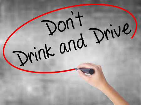 Woman Hand Writing Dont Drink and Drive with black marker over transparent board. Isolated on grey. Life, technology, internet concept. Stock Image