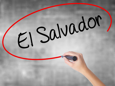Woman Hand Writing El Salvador with black marker over transparent board. Isolated on grey. Business concept. Stock Photo Stock Photo