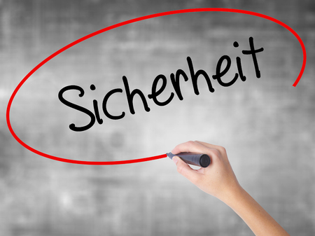 sicherheit: Woman Hand Writing Sicherheit (Safety in German) with black marker over transparent board. Isolated on grey. Business,  internet concept. Stock Photo