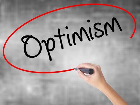 Woman Hand Writing Optimism  with black marker over transparent board. Isolated on grey. Business concept. Stock Photo
