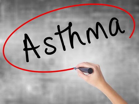 Woman Hand Writing Asthma with black marker over transparent board. Isolated on grey. Business concept. Stock Photo