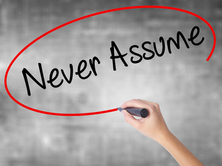presuming: Woman Hand Writing Never Assume with black marker over transparent board. Isolated on grey. Business concept. Stock Photo Stock Photo