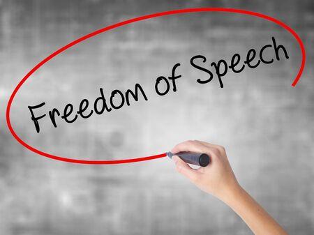 Escritura de la mano de la mujer Libertad de expresión con marcador negro sobre tablero transparente. Aislado en gris Concepto de negocio. Foto de stock Foto de archivo