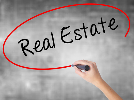 evaluating: Woman Hand Writing Real Estate  with black marker over transparent board. Isolated on grey. Business concept. Stock Photo