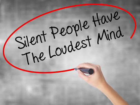 Woman Hand Writing Silent People Have The Loudest Mind with black marker over transparent board. Isolated on grey. Business concept. Stock Photo Stock Photo