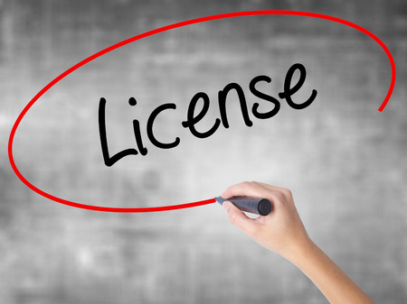 Woman Hand Writing License with black marker over transparent board. Isolated on grey. Business concept. Stock Photo