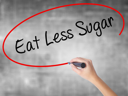 Woman Hand Writing Eat Less Sugar  with black marker over transparent board. Isolated on grey. Business concept. Stock Photo
