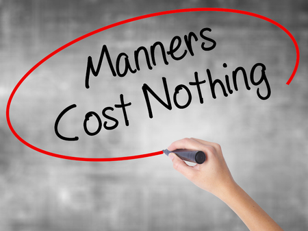 manners: Woman Hand Writing Manners Cost Nothing with black marker over transparent board. Isolated on grey. Business concept. Stock Photo