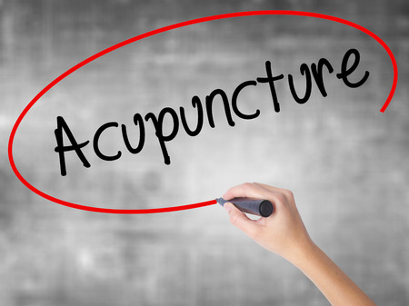 massage symbol: Woman Hand Writing Acupuncture with black marker over transparent board. Isolated on grey. Business concept. Stock Photo Stock Photo