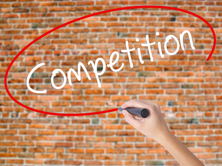 business pitch: Woman Hand Writing Competition  with black marker on visual screen. Isolated on bricks. Business concept. Stock Photo