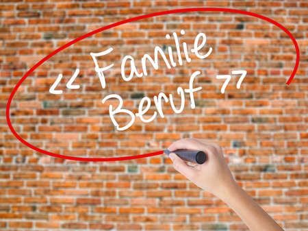 Woman Hand Writing familie beruf (Family Occupation in German) with black marker on visual screen. Isolated on bricks. Business concept. Stock Photo