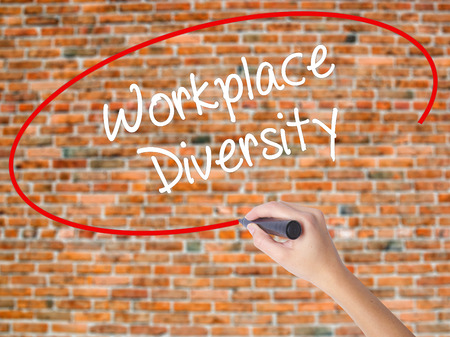 Woman Hand Writing Workplace Diversity  with black marker on visual screen. Isolated on bricks. Business concept. Stock Photo