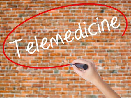 users video: Woman Hand Writing Telemedicine with black marker on visual screen. Isolated on bricks. Business concept. Stock Photo