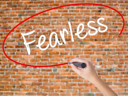 active arrow: Woman Hand Writing Fearless  with black marker on visual screen. Isolated on bricks. Business concept. Stock Photo Stock Photo