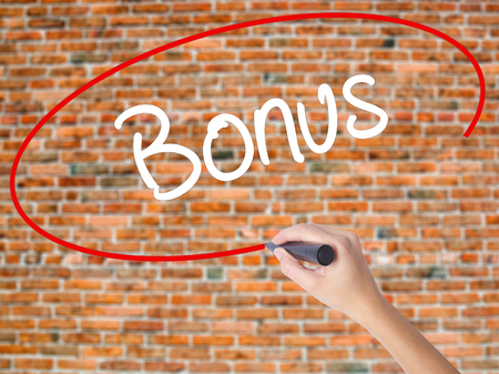 Woman Hand Writing Bonus with black marker on visual screen. Isolated on bricks. Business concept. Stock Photo