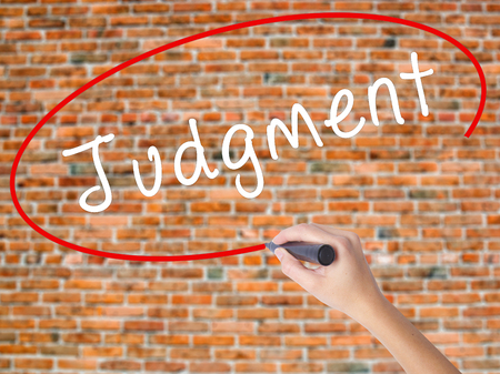 Woman Hand Writing Judgment with black marker on visual screen. Isolated on bricks. Business concept. Stock Photo