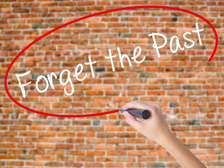 Escritura de la mano de mujer Olvide el pasado con marcador negro en la pantalla visual. Aislado en ladrillos. Concepto de negocio. Foto de stock Foto de archivo