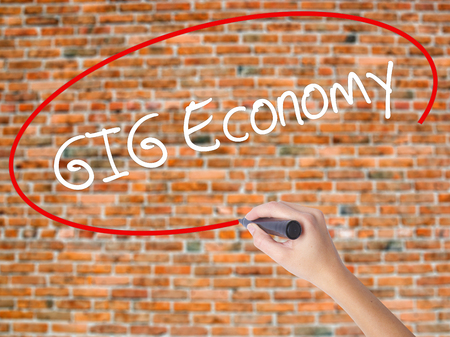 Woman Hand Writing GIG Economy with black marker on visual screen. Isolated on bricks. Business concept. Stock Photo