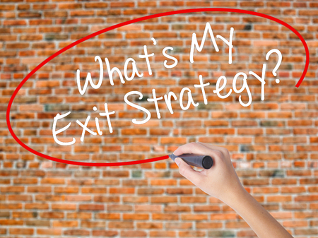 Woman Hand Writing Whats My Exit Strategy? with black marker on visual screen. Isolated on bricks. Business concept. Stock Photo