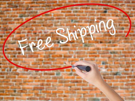 Woman Hand Writing Free Shipping with black marker on visual screen. Isolated on bricks. Business concept. Stock Photo Stock Photo