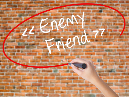 Woman Hand Writing Enemy - Friend with black marker on visual screen. Isolated on bricks. Business concept. Stock Photo