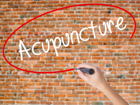 alternative practitioner: Woman Hand Writing Acupuncture with black marker on visual screen. Isolated on bricks. Business concept. Stock Photo
