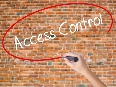 Woman Hand Writing Access Control with black marker on visual screen. Isolated on bricks. Business concept. Stock Photo
