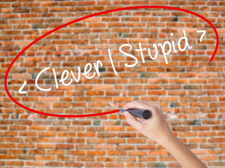 stupidity: Woman Hand Writing Clever - Stupid with black marker on visual screen. Isolated on bricks. Business concept. Stock Photo