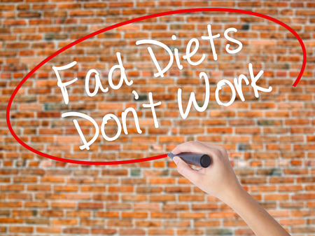 Woman Hand Writing Fad Diets Dont Work with black marker on visual screen. Isolated on bricks. Business concept. Stock Photo