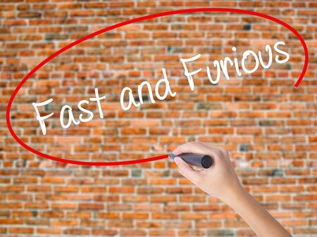 quickness: Woman Hand Writing Fast and Furious with black marker on visual screen. Isolated on bricks. Business concept. Stock Photo