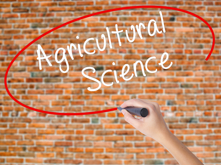 agronomist: Woman Hand Writing Agricultural Science with black marker on visual screen. Isolated on bricks. Business concept. Stock Photo Stock Photo