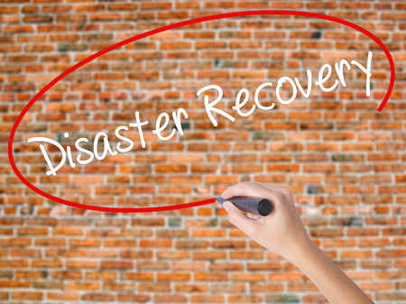 Woman Hand Writing Disaster Recovery with black marker on visual screen. Isolated on bricks. Business concept. Stock Photo