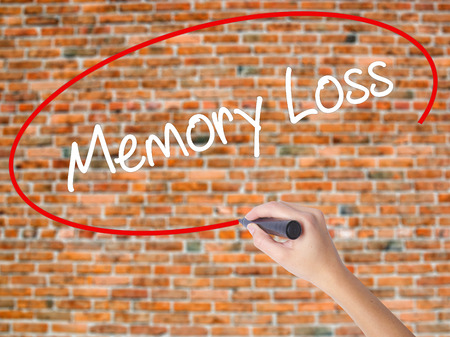 Woman Hand Writing Memory Loss with black marker on visual screen. Isolated on bricks. Business concept. Stock Photo