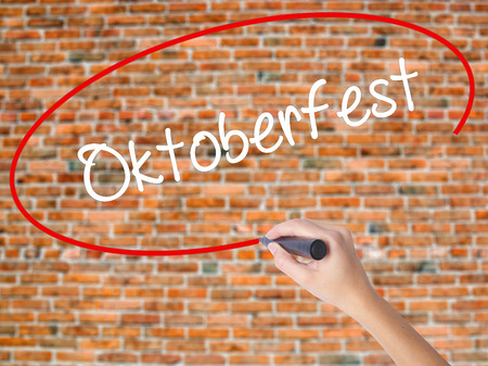 Woman Hand Writing Oktoberfest with black marker on visual screen. Isolated on bricks. Business concept. Stock Photo