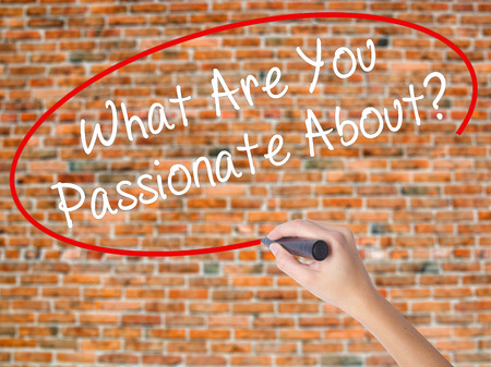 optimismo: Woman Hand Writing What Are You Passionate About?  with black marker on visual screen. Isolated on bricks. Business concept. Stock Photo Foto de archivo