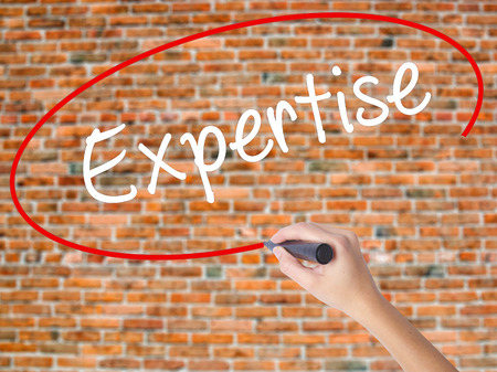 common goal: Woman Hand Writing Expertise with black marker on visual screen. Isolated on bricks. Business concept. Stock Photo Stock Photo