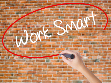 workday: Woman Hand Writing Work Smart with black marker on visual screen. Isolated on bricks. Business concept. Stock Photo