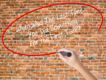 Woman Hand Writing When Was The Last Time You Did Something for the First Time? with black marker on visual screen. Isolated on bricks. Business concept. Stock Photo Stock Photo