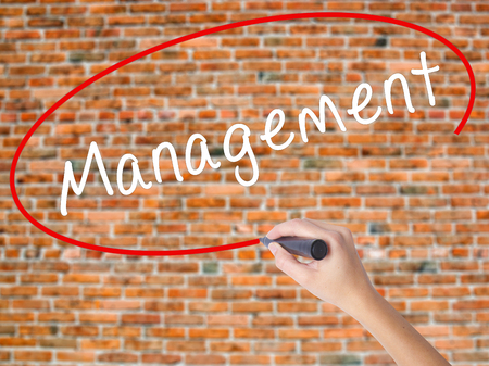 Woman Hand Writing Management with black marker on visual screen. Isolated on bricks. Business concept. Stock Photo