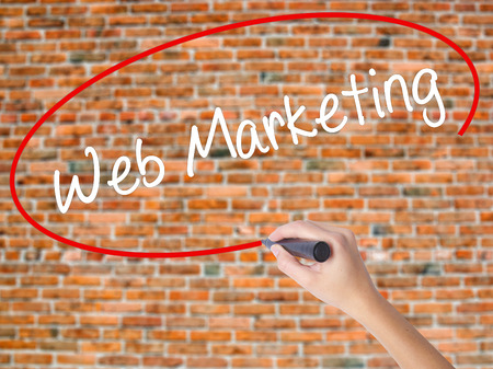 Woman Hand Writing Web Marketing with black marker on visual screen. Isolated on bricks. Business concept. Stock Photo