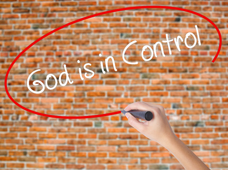 Woman Hand Writing God is in Control with black marker on visual screen. Isolated on bricks. Business concept. Stock Photo