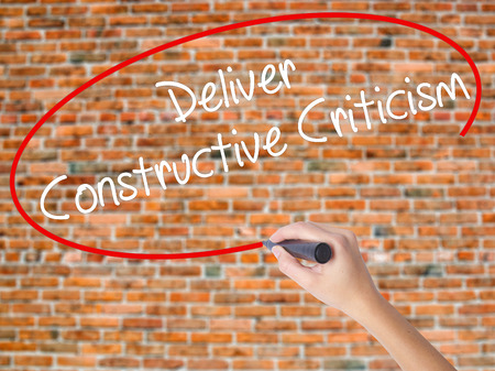 Woman Hand Writing Deliver Constructive Criticism with black marker on visual screen. Isolated on bricks. Business concept. Stock Photo