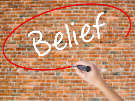 Woman Hand Writing Belief with black marker on visual screen. Isolated on bricks. Business concept. Stock Photo
