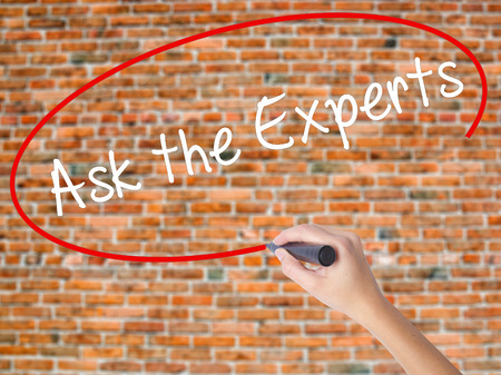 warranty questions: Woman Hand Writing Ask the Experts with black marker on visual screen. Isolated on bricks. Business concept. Stock Photo Stock Photo