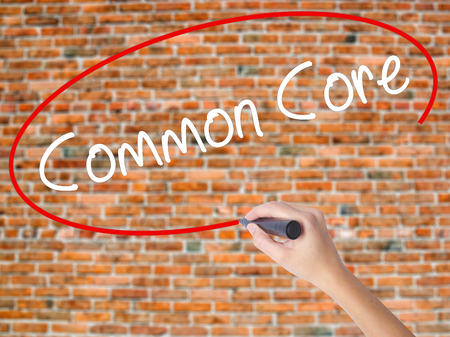 rigorous: Woman Hand Writing Common Core with black marker on visual screen. Isolated on bricks. Education, technology, internet concept. Stock Image Stock Photo