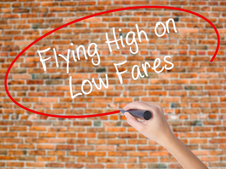 Woman Hand Writing Flying High on Low Fares with black marker on visual screen. Isolated on bricks. Business concept. Stock Photo Stock Photo
