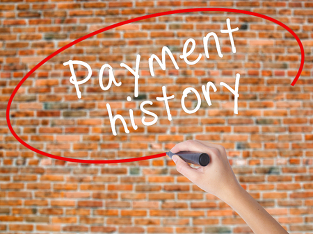 Woman Hand Writing Payment history with black marker on visual screen. Isolated on bricks. Business concept. Stock Photo Stock Photo