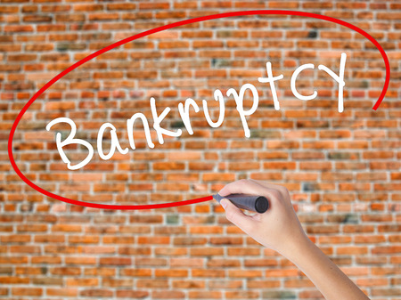 Woman Hand Writing Bankruptcy with black marker on visual screen. Isolated on bricks. Business concept. Stock Photo