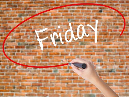 Woman Hand Writing Friday with black marker on visual screen. Isolated on bricks. Business concept. Stock Photo Stock Photo