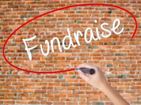 Woman Hand Writing Fundraise with black marker on visual screen. Isolated on bricks. Business,  technology, internet concept. Stock Photo
